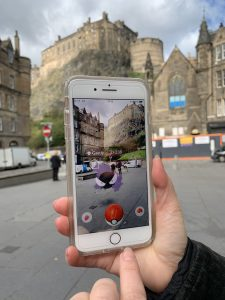 Photo of someone playing Pokémon Go in the Grassmarket, with Edinburgh Castle in the background.